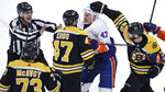 New York Islanders right wing Leo Komarov, second from right, tangles with Boston Bruins defenseman Torey Krug, second from left, as he is surrounded by Bruins during first period of an NHL hockey game in Boston, Tuesday, Feb. 5, 2019. From left are Boston Bruins defenseman Charlie McAvoy (73), Krug, Komarov and center David Krejci (46). (AP Photo/Charles Krupa)