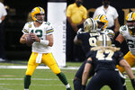 Green Bay Packers quarterback Aaron Rodgers (12) drops back to pass under pressure from New Orleans Saints defensive lineman Malcom Roach in the first half of an NFL football game in New Orleans, Sunday, Sept. 27, 2020. (AP Photo/Butch Dill)