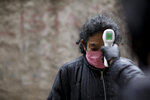 A volunteer measures the temperature of a resident inside the Fraga slum during a government-ordered lockdown to curb the spread of the new coronavirus, in Buenos Aires, Argentina, Saturday, June 6, 2020. (AP Photo/Natacha Pisarenko)