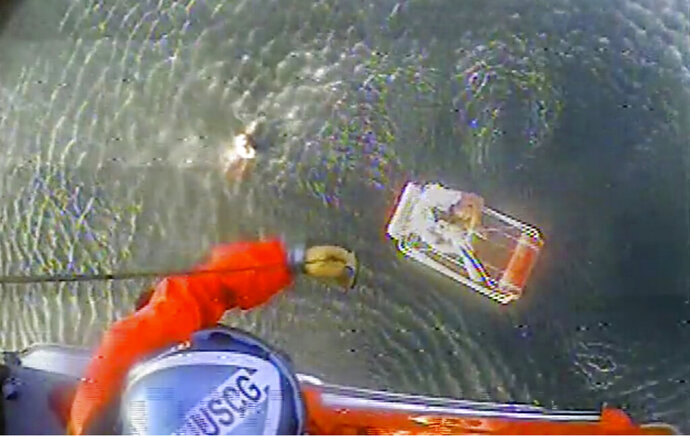 In this Aug. 20, 2019 image provided by the U.S. Coast Guard, a Coast Guard Air Station San Francisco MH-65 Dolphin helicopter crew rescues two people after their plane went down near Half Moon Bay, Calif. A self-professed thrill seeker and pilot was forced to bring down his new plane safely into the ocean off Northern California as it lost power, recording dramatic videos as he and his passenger treaded water in the chilly ocean awaiting rescue. Pilot David Lesh embarked on a flight Tuesday evening over Half Moon Bay south of San Francisco. He's a 34-year-old globe-trotting skier and the founder of a Colorado-based outerwear company Virtik. (U.S. Coast Guard via AP)