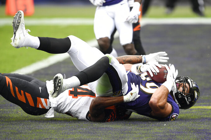 Baltimore Ravens tight end Mark Andrews, top, holds on to the ball while catching a touchdown pass from quarterback Lamar Jackson, not visible, as Cincinnati Bengals strong safety Vonn Bell (24) tries to defend during the first half of an NFL football game, Sunday, Oct. 11, 2020, in Baltimore. (AP Photo/Nick Wass)