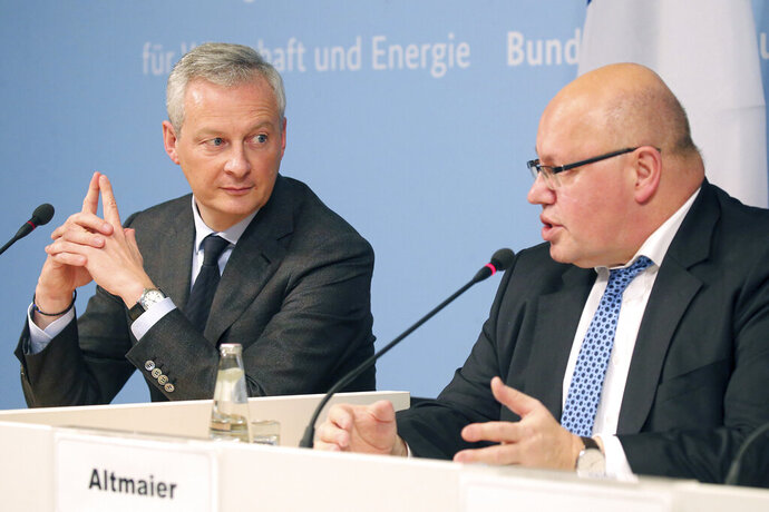 German Economy Minister Peter Altmaier, right, and France's Economy Minister Bruno Le Maire, left, address the media during a joint statement in Berlin, Germany, Tuesday, Feb. 19, 2019. (Wolfgang Kumm/dpa via AP)