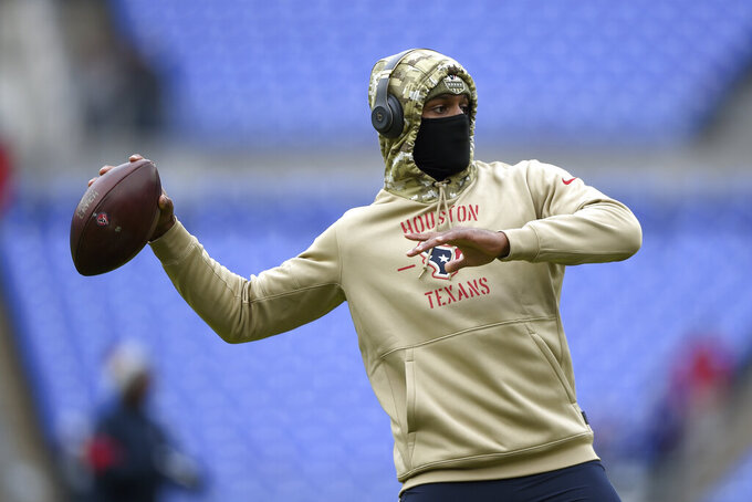 Houston Texans quarterback Deshaun Watson is bundled up while working out prior to an NFL football game against the Baltimore Ravens, Sunday, Nov. 17, 2019, in Baltimore. (AP Photo/Gail Burton)