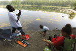 The Hayes family, dad, Tanell Hayes, left, helps daughters Amarianna, 4, and Amaris, 11, get their rods baited and lines in the water as they try to stay cool in the record-breaking heat by fishing from the shadows along the banks of Cheney Lake in Anchorage, Alaska, Friday, July 5, 2019. Alaskans who routinely pack knit caps and fleece jackets in summer on Friday were swapping them for sunscreen and parasols amid a prolonged heatwave.  (Anne Raup/Anchorage Daily News via AP)