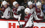 Colorado Avalanche's J.T. Compher (37) is congratulated by teammates after he scored against Minnesota Wild goalie Devan Dubnyk in the first period of an NHL hockey game, Tuesday, March 13, 2018, in St. Paul, Minn. (AP Photo/Jim Mone)