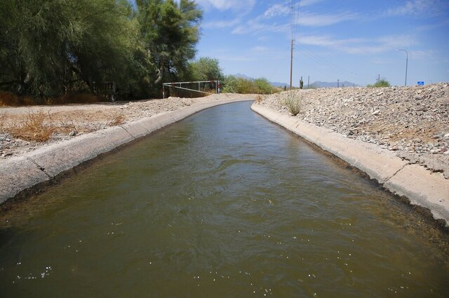 Water flows through this canal Saturday, June 27, 2020, in Laveen, Ariz. Central Arizona has been booming — more people, more houses, more need for water. There's also a long-term drought, and less water to buy from the Central Arizona Project canal system. (AP Photo/Ross D. Franklin)