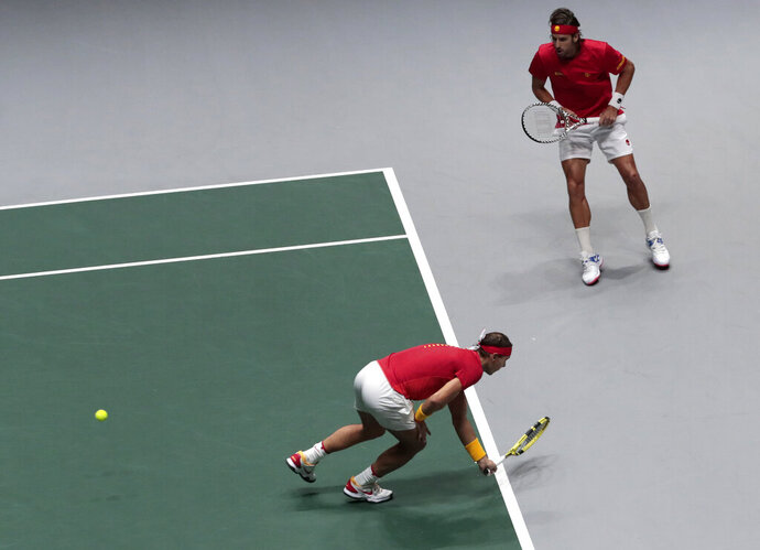 Spain's Rafael Nadal, front, and his partner Feliciano Lopez return to Great Britain's Jamie Murray and Neal Skupski during their Davis Cup semifinal doubles match, in Madrid, Spain, Saturday, Nov. 23, 2019. (AP Photo/Bernat Armangue)