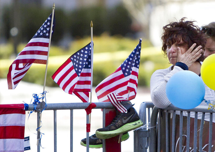 FILE - In this April 22, 2013 file photo, a woman wipes a tear at a memorial for the victims of the Boston Marathon bombing on Boylston Street near the race finish line in Boston.  A federal appeals court has overturned the death sentence of Dzhokhar Tsarnaev in the 2013 Boston Marathon bombing, Friday, July 31, 2020, saying the judge who oversaw the case didn't adequately screen jurors for potential biases.  (AP Photo/Robert F. Bukaty)