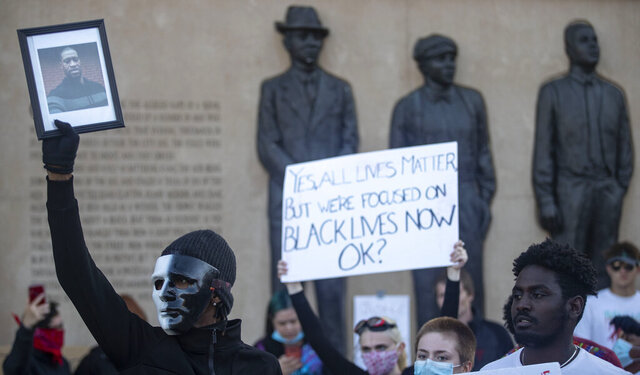 In this May 30, 2020 photo, a protestor holds up a photo of George Floyd in front of the Clayton, Jackson, McGhie Memorial as part of a large protest in Duluth, Minn.  The state's Board of Pardons, consisting of Gov. Tim Walz, Attorney General Keith Ellison and the chief justice of the state's Supreme Court Lorie Skjerven Gildea, will vote Friday, June 12, to clear Max Mason of a rape case that led to the only known lynching of Black people in the state's history 100 years ago next week. (Alex Kormann/Star Tribune via AP)