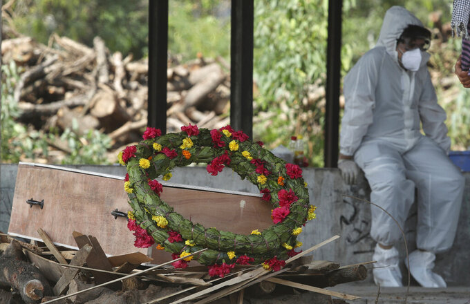 A wreath lies on the coffin of a COVID-19 victim before his cremation in Jammu, India, Friday, April 30, 2021.  Indian scientists appealed to Prime Minister Narendra Modi to publicly release virus data that would allow them to save lives as coronavirus cases climbed again Friday, prompting the army to open its hospitals in a desperate bid to control a massive humanitarian crisis. (AP Photo/Channi Anand)