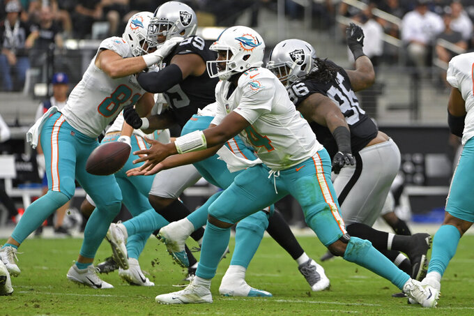 Miami Dolphins quarterback Jacoby Brissett (14) tosses the ball against the Las Vegas Raiders during the first half of an NFL football game, Sunday, Sept. 26, 2021, in Las Vegas. (AP Photo/David Becker)