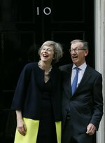 FILE - In this Wednesday, July 13, 2016 file photo, new British Prime Minister Theresa May and her husband Philip May stand on the steps of 10 Downing Street in London. David Cameron stepped down Wednesday after six years as prime minister. (AP Photo/Kirsty Wigglesworth, File)