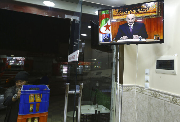 A man closes a restaurant while Algerian President Abdelmadjid Tebboune speaks on television, Thursday, Feb.18, 2021 in Algiers. Algerian President Abdelmadjid Tebboune announced he will dissolve parliament to pave the way for new elections and ordered the release of 32 protesters whose pro-democracy movement pushed out his predecessor two years ago. However he didn't set a date for the elections yet, and protesters want deeper change to Algeria's still-secretive power structure. (AP Photo/Fateh Guidoum)
