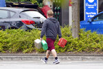 A man carries containers to a petrol station in Bracknell, England, Saturday Sept. 25, 2021. The haulage industry says the U.K. is short tens of thousands of truckers, due to a perfect storm of factors including the coronavirus pandemic, an aging workforce and an exodus of European Union workers following Britain's departure from the bloc. BP and Esso shut a handful of their gas stations this week, and motorists have formed long lines as they try to fill up in case of further disruption. (Steve Parsons/PA via AP)