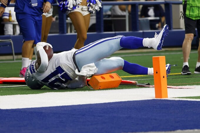Dallas Cowboys running back Ezekiel Elliott (21) lands on sideline equipment after carrying the ball on a running play in the second half of an NFL football game against the New York Giants in Arlington, Texas, Sunday, Oct. 10, 2021. (AP Photo/Ron Jenkins)