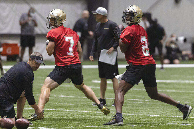 New Orleans Saints quarterbacks  quarterback Taysom Hill (7) and  Jameis Winston (2) run drills during NFL football training camp in Metairie, Thursday, July 29, 2021. (AP Photo/Derick Hingle)