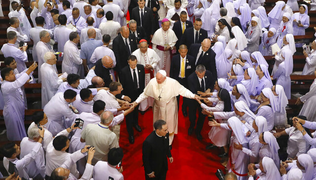 Priests, religious seminarians and Catechists touch the hands of Pope Francis as he leaves after meeting them at Saint Peter's Parish on the outskirts of Bangkok, Thailand, Friday, Nov. 22, 2019. Pope Francis urged more efforts to combat the