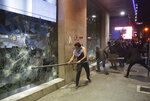 FILE - In this Tuesday, Jan. 14, 2020 file photo, anti-government protesters smash a bank widows, during ongoing protests against the Lebanese central bank's governor and against the deepening financial crisis, at Hamra trade street, in Beirut, Lebanon. For years, many Lebanese have lived beyond their means, supporting their out-sized spending with loans and remittances from diaspora relatives. A severe financial crisis and unprecedented capital controls have put a stop to this, uniting rich and poor in anger against a banking system they accuse of holding their deposits hostage. (AP Photo/Hussein Malla, File)