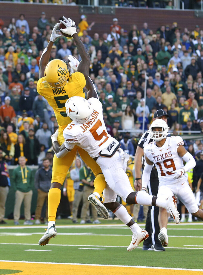 Baylor wide receiver Denzel Mims (5) makes a touchdown reception over Texas defensive back D'Shawn Jamison (5) in the third quarter in an NCAA college football game Saturday, Nov. 23, 2019, in Waco, Texas. (AP Photo/Richard W. Rodriguez)