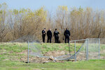 Corona Police officers survey the site where an airplane crashed and burned in a ditch next to the runway after taking off at Corona Municipal Airport in Corona on Wednesday, Jan. 22, 2020. (Watchara Phomicinda/The Orange County Register via AP)