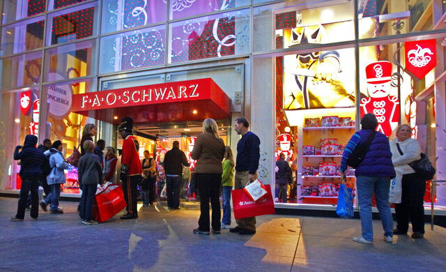 FILE -In this Nov. 21, 2011 file photo, shoppers pause outside of the Fifth Avenue FAO Schwarz in New York. Under Armour said Tuesday, Feb. 11, 2020, that it may scuttle the opening of its flagship store inside the space formerly occupied by the iconic FAO Schwarz toy store in New York City. (AP Photo/Bebeto Matthews, File)