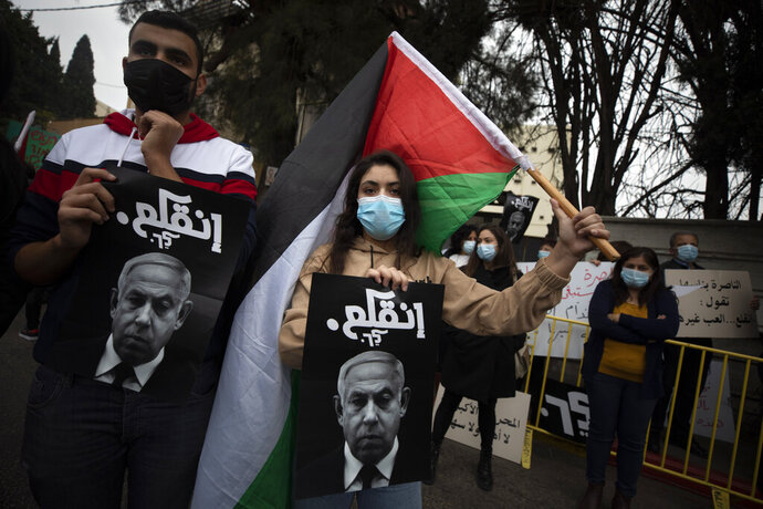 Palestinian protesters hold signs and flags during a demonstration against a visit of Israeli Prime Minister Benjamin Netanyahu to the northern Arab city of Nazareth, Israel, Wednesday, Jan. 13, 2021. Netanyahu, who has spent much of his long career casting Israel's Arab minority as a potential fifth column led by terrorist sympathizers, is now openly courting their support as he seeks reelection in the country's fourth vote in less than two years. (AP Photo/Sebastian Scheiner)