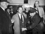 FILE - This Dec. 7, 1941 file photo shows a Japanese man under arrest in the roundup at Norfolk, Va., being searched by a policeman after Japan's declaration of war on the U.S. Beliefs that Hispanics and Asians living in the U.S. won't assimilate or refuse to speak English are based on stereotypes that scholars say are linked to notions of white supremacy. Throughout American history, Hispanics and Asians have been pressured to adopt the customs of the mainstream white population. The pressure came even as some laws forbade them from voting, intermarrying and having access to education and public facilities. (AP Photo, File)