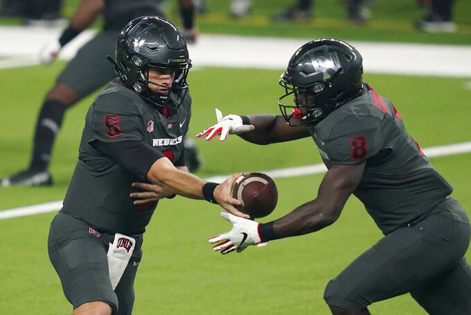UNLV quarterback Max Gilliam (6) hands the ball off to running back Charles Williams (8) during the first half of the team's NCAA college football game against Nevada, Saturday, Oct. 31, 2020, in Las Vegas. (AP Photo/John Locher)