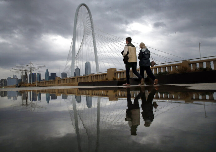 As clouds from a passing shower move across the Dallas skyline and the Margaret Hunt Hill Bridge, Michael McKinney and Maddi Reid of Dallas take a stroll across the Continental Street Bridge in Dallas on the their fourth wedding anniversary, Friday, Jan. 10, 2020. The national Storm Prediction Center said more than 18 million people in Louisiana, Arkansas, Texas and Oklahoma were at an enhanced risk of storms Friday, including from strong tornadoes, flooding rains and wind gusts that could exceed 80 mph (129 kph), the speed of a Category 1 hurricane. (Tom Fox/The Dallas Morning News via AP)