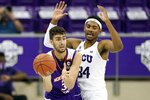 Northwestern State forward Robert Chougkaz (34) throws a pass as TCU forward Kevin Easley, right, defends during the second half of an NCAA college basketball game in Fort Worth, Texas, Thursday, Dec. 3, 2020. (AP Photo/Tony Gutierrez)