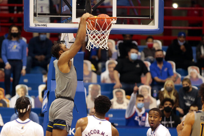 West Virginia junior forward Derek Culver dunks on Kansas in the second half of an NCAA college basketball game, Tuesday, Dec. 22, 2020, in Lawrence, Kan. (Evert Nelson/The Topeka Capital-Journal via AP)
