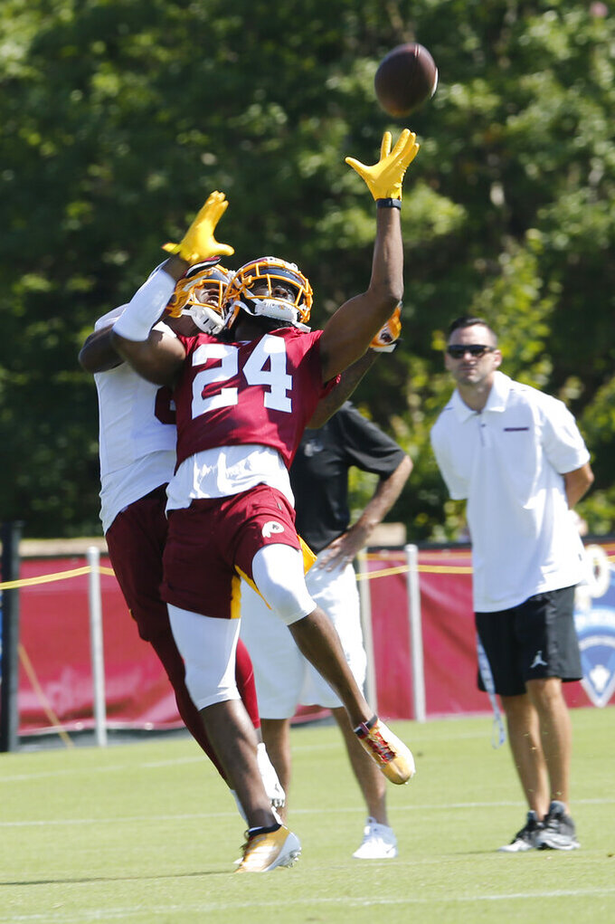 Washington Redskins cornerback Josh Norman (24) intercepts a pass intended for wide receiver Darvin Kidsy (84) during the first day of NFL football training camp in Richmond, Va., Thursday, July 25, 2019. (AP Photo/Steve Helber)
