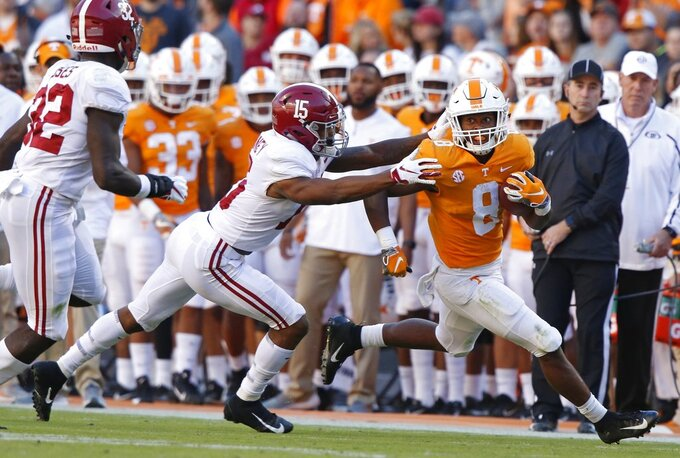 Tennessee running back Ty Chandler (8) runs for yardage as he's grabbed by Alabama defensive back Xavier McKinney (15) in the first half of an NCAA college football game Saturday, Oct. 20, 2018, in Knoxville, Tenn. (AP Photo/Wade Payne)