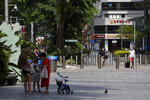People wearing protective face masks walk along the Orchard Road shopping belt in Singapore, Friday, April 10, 2020. The Singapore government put in place