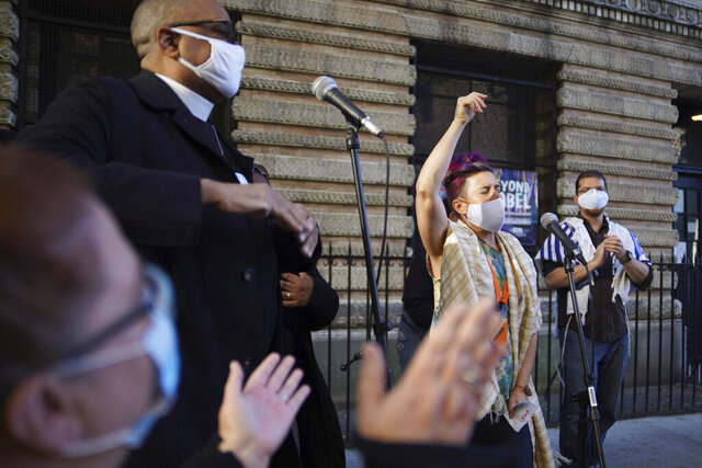 Shira Kline, a director of worship for Lab/Shul, a Jewish community-based organization, leads a group in song during an interfaith gathering outside of the Judson Memorial Church near Washington Square Park in New York, Wednesday, Nov. 4, 2020. Muslims, Jews, Christians and Buddhists came together to show solidarity among faith communities as the country awaits the final result of the U.S. presidential election. (AP Photo/Emily Leshner)