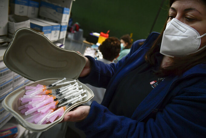 A health worker prepares Pfizer vaccines before people receive a shot during a COVID-19 vaccination campaign, in Pamplona, northern Spain, Friday, May 7, 2021.(AP Photo/Alvaro Barrientos)