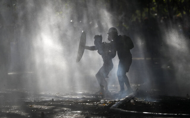 Anti-government demonstrators shield themselves amid the spray of a police water cannon trying to disperse them in Santiago, Chile, Friday, Dec. 27, 2019. Chile has been roiled by continuing and sometimes violent street protests since Oct. 18, when a student protest over a modest increase in subway fares turned into a much larger and broader movement with a long list of demands that largely focus on inequality. (AP Photo/Fernando Llano)