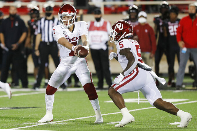 Oklahoma quarterback Spencer Rasttler hands off to running back T.J. Pledger during the second half of an NCAA college football game, Saturday, Oct. 31, 2020, in Lubbock, Texas. (AP Photo/Mark Rogers)