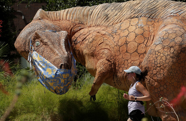 A jogger runs past a mask clad Acrocanthosaurus at the Witte Museum in San Antonio, Thursday, May 28, 2020. The museum has been closed due to the COVID-19 pandemic and is scheduled to reopen May 30th. (AP Photo/Eric Gay)