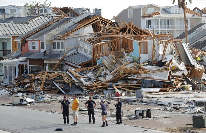 FILE- In this Oct. 11, 2018 file photo, rescue personnel perform a search in the aftermath of Hurricane Michael in Mexico Beach, Fla. A year after Hurricane Michael, Bay County, Florida, is still in crisis. Thousands are homeless, medical care and housing are at a premium, and domestic violence is increasing. Michael was among the strongest hurricanes ever to make landfall in the United States. This summer, county officials unveiled a blueprint to rebuild. Among their ideas: Use shipping containers and 3-D technology to build new houses and offer signing bonuses to lure new doctors.  (AP Photo/Gerald Herbert, File)