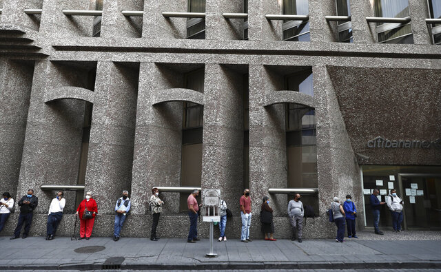 Bank customers keep their distance to help curb the spread of the new coronavirus, as they stand in line outside a bank in Mexico City, Monday, June 29, 2020. Mexico City is moving this week to the next stage of its gradual reopening from its COVID-19 pandemic lockdown. (AP Photo/Eduardo Verdugo)