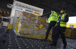 Cargo workers move a palette of cool boxes and other items into a pharma transport container during a demonstration on the handling and logistics of vaccines and medicines at the DHL cargo warehouse in Steenokkerzeel, Belgium, Tuesday, Dec. 1, 2020. European Commission President Ursula von der Leyen said Tuesday that member states have started working on their vaccination plans and on the logistics for the delivery of tens of millions of doses across the 27-nation bloc. Safely delivering COVID-19 vaccines, once approval has been made, will be the mission of the century for the global air cargo industry. (AP Photo/Virginia Mayo)