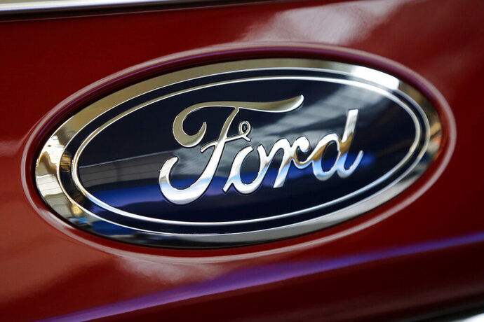 FILE- This Feb. 15, 2018, photo shows a Ford logo on a 2018 Expedition 4x4 on display at the Pittsburgh Auto Show. Ford says that next year it will start equipping redesigned models to get software updates over the internet or cellular phone connections. The company says all of its models will get the feature as they are redesigned. It will reduce visits to dealers for service and even computer-related recall repairs. Owners will be able to opt in to the program and get updates over their home wireless network at no cost. The cost for cellular updates has not been announced.  (AP Photo/Gene J. Puskar, File)