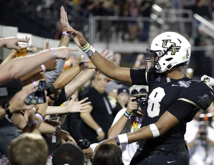 Central Florida quarterback Darriel Mack Jr., right, high fives fans after scoring a touchdown against Memphis during the second half of the American Athletic Conference championship NCAA college football game, Saturday, Dec. 1, 2018, in Orlando, Fla. (AP Photo/John Raoux)