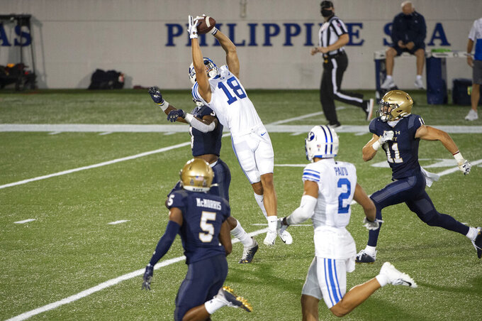 BYU wide receiver Gunner Romney (18) leaps to catch a pass over Navy defensive back Cameron Kinley during the second half of an NCAA college football game, Monday, Sept. 7, 2020, in Annapolis, Md. (AP Photo/Tommy Gilligan)
