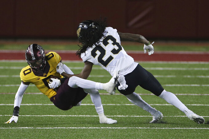 Minnesota wide receiver Rashod Bateman (0) falls after catching a pass, next to Purdue safety Cory Trice (23) during the second half of an NCAA college football game Friday, Nov. 20, 2020, in Minneapolis. Minnesota won 34-31. (AP Photo/Stacy Bengs)