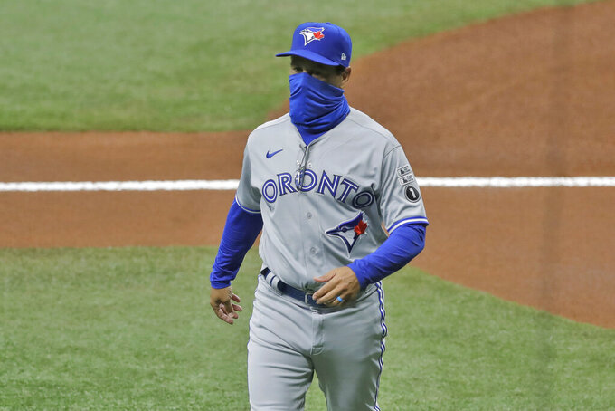 Toronto Blue Jays manager Charlie Montoya wears a protective face mask as he walks back to the dugout after delivering the line up card before a baseball game against the Tampa Bay Rays Friday, July 24, 2020, in St. Petersburg, Fla. (AP Photo/Chris O'Meara)