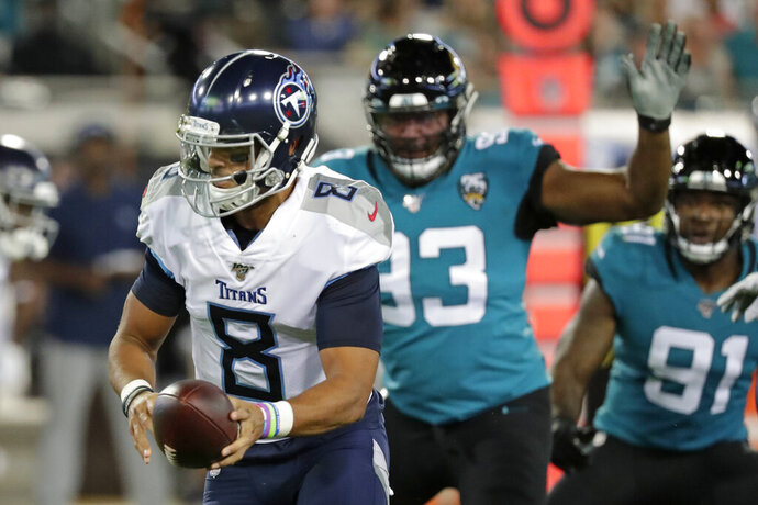 Tennessee Titans quarterback Marcus Mariota (8) looks to hand off the ball as he is pressured by Jacksonville Jaguars defensive end Calais Campbell, right, during the first half of an NFL football game, Thursday, Sept. 19, 2019, in Jacksonville, Fla. (AP Photo/John Raoux)