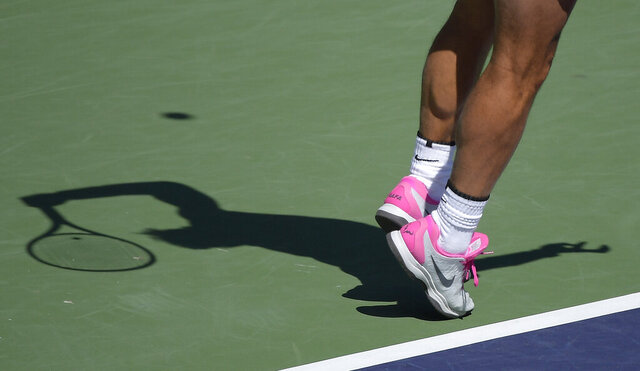 FIEL - In this March 12, 2019, file photo, Rafael Nadal, of Spain, casts a shadow as he serves to Diego Schwartzman at the BNP Paribas Open tennis tournament in Indian Wells, Calif. The ATP called off all men's professional tennis tournaments for six weeks because of the COVID-19 pandemic, but a WTA spokeswoman told The Associated Press on Thursday, March 12, 2020, that the women's tour was not immediately prepared to do the same. (AP Photo/Mark J. Terrill, File)