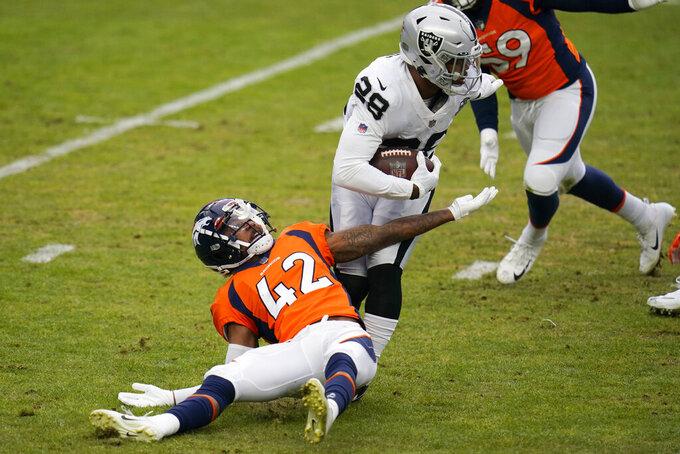Las Vegas Raiders running back Josh Jacobs (28) runs against Denver Broncos cornerback Parnell Motley during the first half of an NFL football game, Sunday, Jan. 3, 2021, in Denver. (AP Photo/Jack Dempsey)